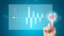 Mano di donna che che indica un punto sullo schermo, in cui c'è un grafico digitale, rappresentato da un cuore