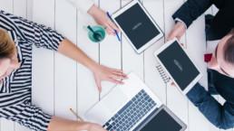 Colleghi in fase di brainstorming / riunione che utilizzano software gestionale su tablet e notebook su tavolo di legno bianco