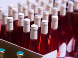 Bottiglie di alcolici di colore rosso con capsula bianca