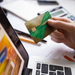 Mano di donna di fronte ad un notebook con una carta di credito in mano