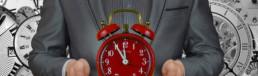 Il Moment Marketing: importante per avere successo - Uomo d'affarti o Business Man che tiene in mano una Sveglia di colore Rosso